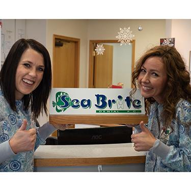 Misty and Sam holding Sea Brite Dental sign