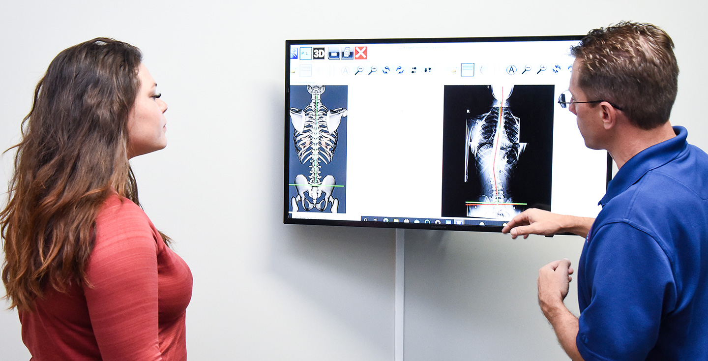 Chiropractor and Patient checking examing X-ray