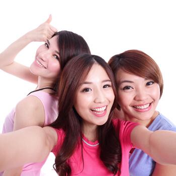 Three young Asian women smiling