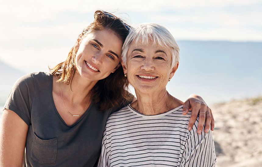 Two woman smiling with heads together