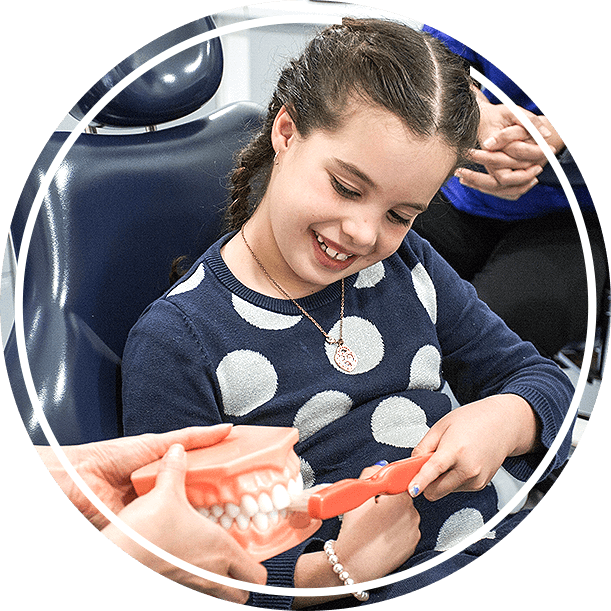Young girl brushing model of teeth