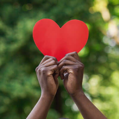 person holding a paper heart