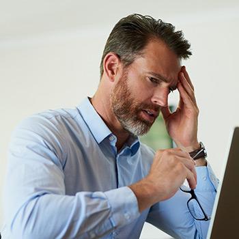 man holding head in dizziness