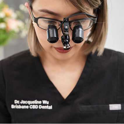 Dr Jacqui Wu wearing magnifying glasses