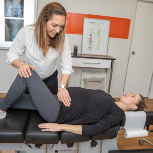 Female chiropractor adjusting female patient's lower back