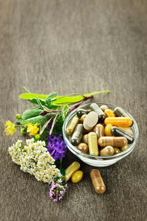 Herbs, flowers and bowl of natural supplements
