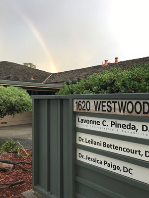 Office sign with rainbow in sky above