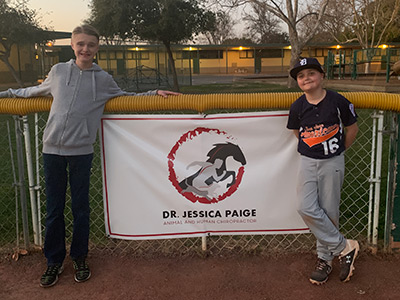softball team members standing in front of our banner