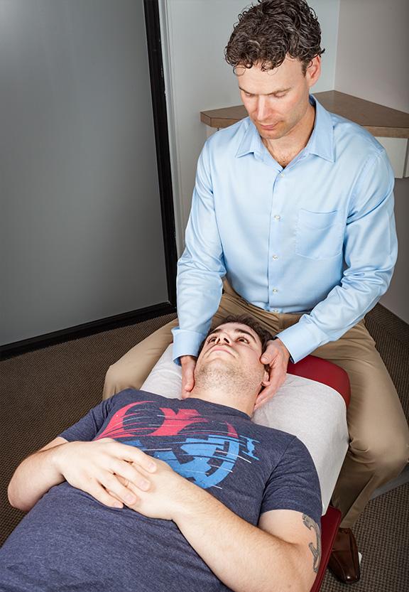 doctors hands on mans head