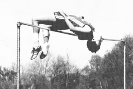 Dr. Smith hurdeling the high jump.