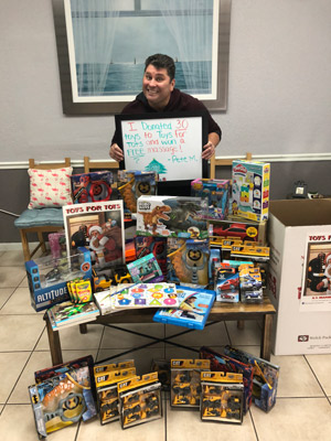 A chiropractic patient surrounded by toys he donated