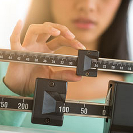 woman checking weight on scale