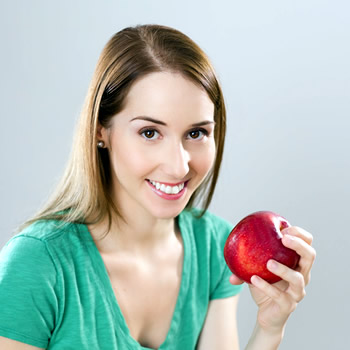 woman smiling with apple at hand
