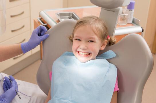 Smiling girl in dentist chair
