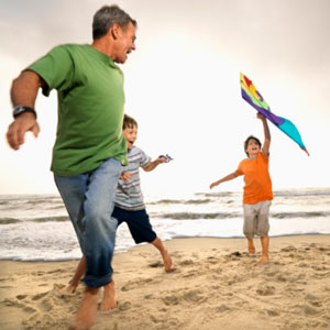 Father and sons running on the beach barefoot.