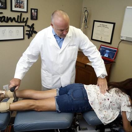 Dr. Scott adjusting woman on table