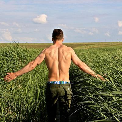 man's back walking in the field