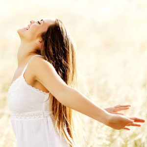 woman outdoors with her arms outstretched, smiling