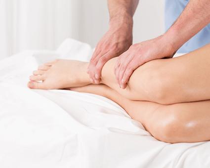therapist massaging womans legs