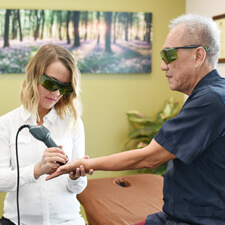 Dr Anna performing laser therapy on a patient's hand