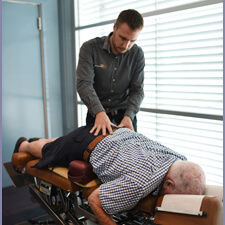 Dr Stott adjusting lower back of male patient