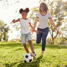 Mom playing soccer with daughter