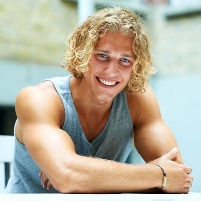 Young handsome curly hair man smiling