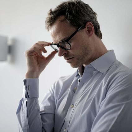 man stressed wearing eyeglasses
