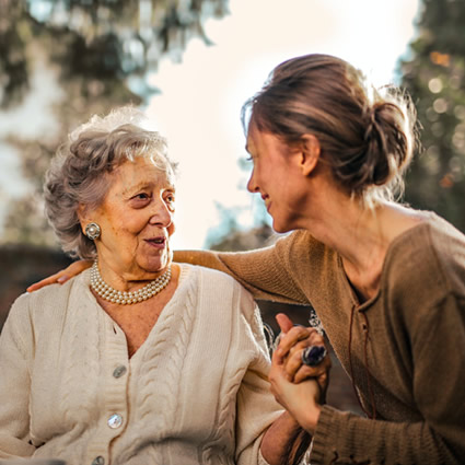 old woman and daughter holding hands smiling