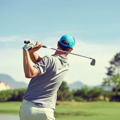 man golfing in a blue hat