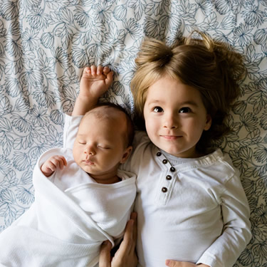infant and little girl lying on bed