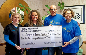 Dr. Kari with a check for the Riverbend Down Syndrome Association