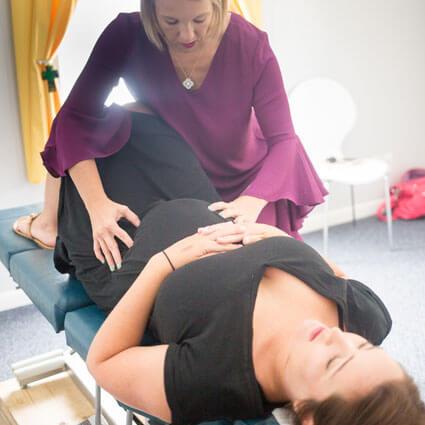 Dr. Cassidie adjusting pregnant mom