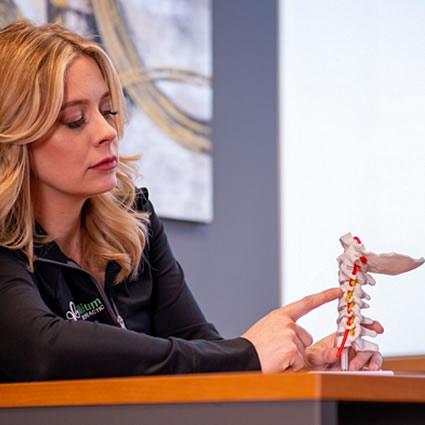Dr. Katelyn pointing to spine model