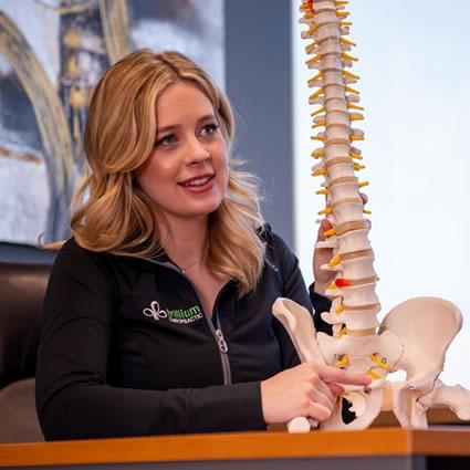 Dr. Katelyn holding spine model