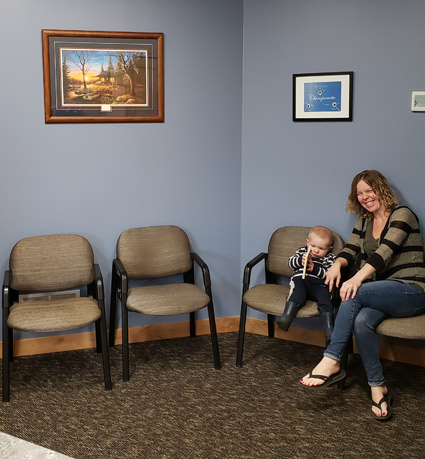 A laughing mother with her baby in the waiting area