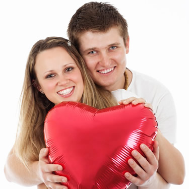Couple hugging and holding red heart balloon
