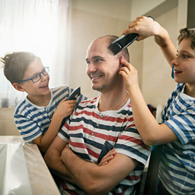 Dad getting haircut by two sons