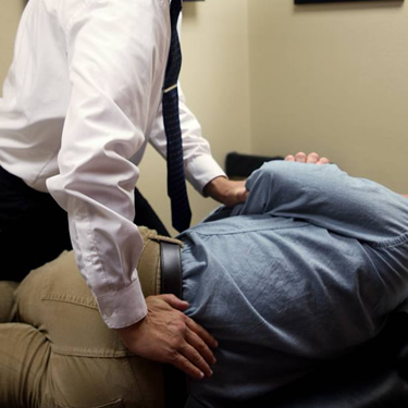Dr Giddings adjusting male patient