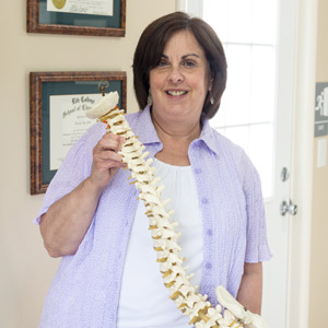 A woman holding a model of a spine.