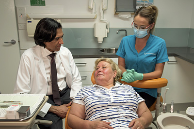 Dentist and tech consult with patient