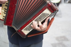 Mid section view of a man holding accordion