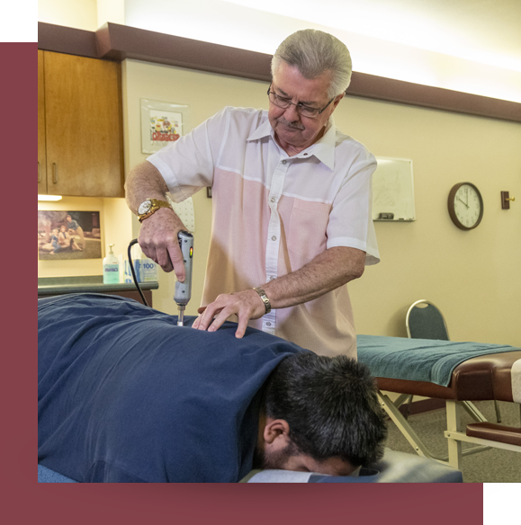 Dr. Shows using Activator on patients back