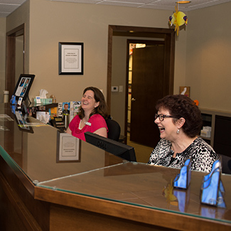 Staff at front desk laughing