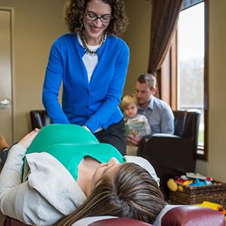 Dr. Cindy adjusting pregnant mom