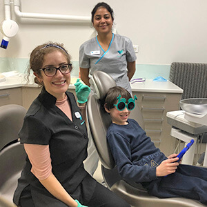 Child in dental chair with glasses on