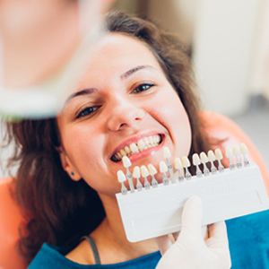 Woman checking tooth whiteness with dentist