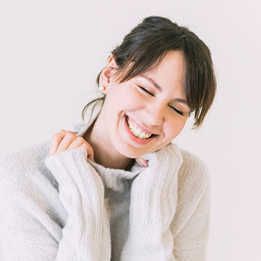 woman in a white sweater, smiling