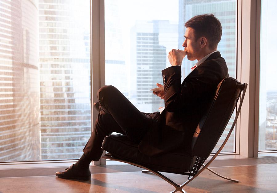 Man drinking and sitting facing window