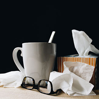 box of tissues next to a cup of tea